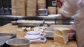 Motion of people are kneading the dough and weighting it before it to be made dumplings. In Taipei Taiwan stock footage
