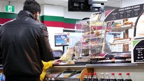 Motion of people line up for paying food at 7 eleven check out counter