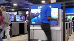 Motion of people looking for a new tv inside electronic store