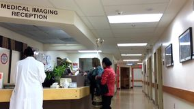 Motion of people at medical imaging reception area stock video