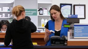 Motion of people paying medicine at pharmacy section. Inside Walmart store