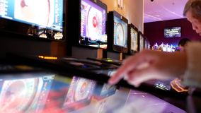 Motion of people playing casino roulette on machine with reflection spinning ball on screen. Inside Casino stock footage