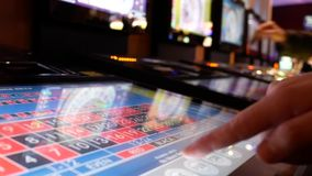 Motion of people playing casino roulette on machine with reflection spinning ball on screen. Inside Casino stock video