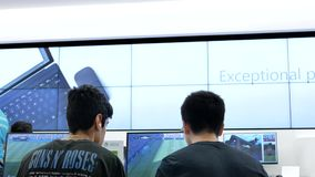 Motion of people playing xbox game at Microsoft store stock footage