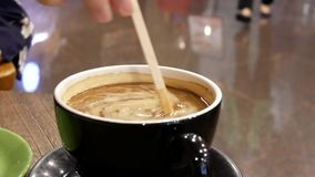 Motion of people putting cream and stirring coffee. Inside coffee shop stock video footage