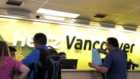 Motion of people renting car in front of Hertz rental company stock video footage