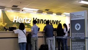Motion of people renting car in front of Hertz rental company stock footage