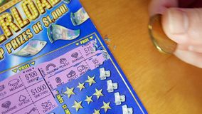 Motion of people scratching lottery ticket at home stock video footage
