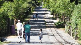 Motion of people strolling beside tour train railway. Inside Vancouver zoo stock video footage