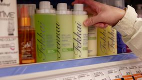 Motion of people taking brilliant glossing shampoo and conditioner. Inside Shoppers drug mart store stock video footage