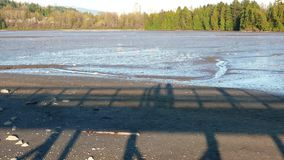Motion of people walking on dock with river reflection shadow. At Rocky point park stock video footage