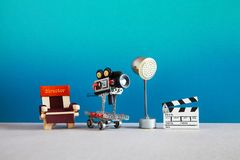 Motion picture backstage area with director`s chair, camera or camcorder on wheels, the lighting projector spotlight and. Clapperboard. Filmmaking behind the royalty free stock photo