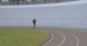 Motion portrait of adult caucasian sporty male runner jogging on the stadium in the urban city outdoors stock footage