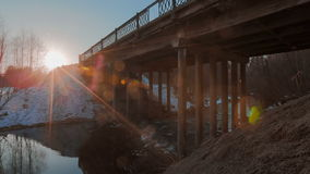 Motion of the river under the bridge against the backdrop of the bright sun. Time lapse video. Motion of the river under the bridge against the backdrop of the stock footage