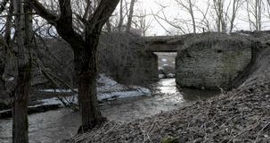 Motion of the river under a stone bridge in spring.  stock video footage