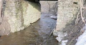 Motion of the river under a stone bridge in spring.  stock video