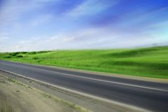 Motion road. Motion blurred road under a cloudy with blue blue sky Royalty Free Stock Photos