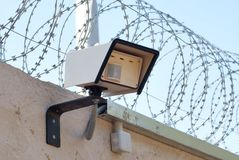 Motion sensor. Motion detector on the wall with barbed wire on the background of the sky Stock Photos