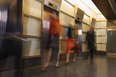 Motion shot of businesspeople walking past elevators Stock Images