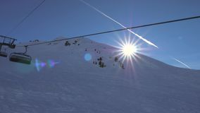 In motion on a ski chair lift in the mountains the sun shines and sunset. In movement, on the ski chair lift, to the top of the snow mountain, the bright sun stock video footage
