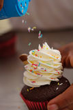 Motion of sprinkles falling on to a cupcake Stock Photo
