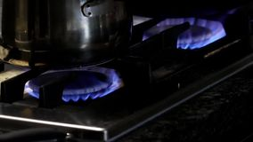 Motion of stainless steel pot on gas oven stock video