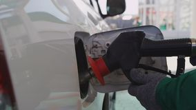 Motion to Technician Putting Gun into Car Gas Tank. Closeup motion aside from car red backlight to technician putting gun into auto gas tank at gasoline station stock footage