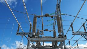 Motion between transformer supports against sky. Bottom view motion between electrical transformer metal supports with high voltage cables on top against sky stock video