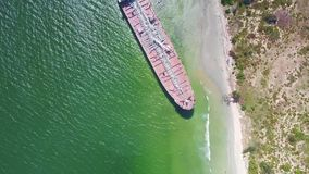 Motion from Transparent Ocean Water to Aground Tanker at Beach. Drone moves from transparent azure ocean water at sand beach to modern tanker aground after stock video footage