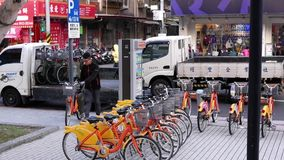 Motion of truck unloading public rental bike call ubike beside and stocking on road. Ubike is a popular network of rental bicycle in Taipei, Taiwan stock video
