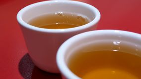 Motion of two cups of hot tea on table inside Chinese restaurant