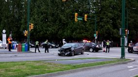 Motion of vehicles are wrecked in a car accident surround people on a city street.