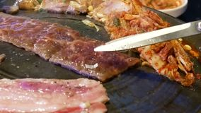 Motion of waitress cooking bbq meat for customer on table. Inside Korean restaurant stock footage