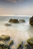 Motion waves on stones at the beach. Stock Image