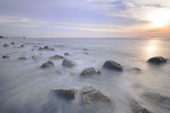 Motion waves on stones at the beach. Stock Photo