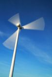 Motion wind turbine in windy day. Motion blade of modern win turbine in windy day with blue sky Stock Photo