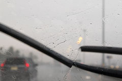Motion of windscreen wipers on windshield with blurred traffic d. Motion of windscreen wipers removing rain drops water on windshield with blurred traffic on royalty free stock images