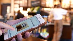 Motion of woman browsing Starbucks drink menu on phone Stock Images
