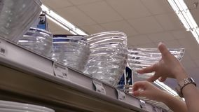 Motion of woman buying glass bowl inside London drugs store. In BC Canada stock video footage
