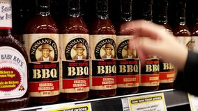 Motion of woman buying Newmans bbq sauce original. Inside buy low foods store stock footage