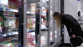 Motion of woman buying pizza inside Walmart store stock video footage