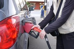 Motion of woman inserting handle from car hole at gas station royalty free stock photo