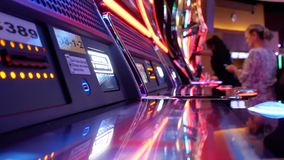 Motion of woman inserts ticket on slot machine inside Casino stock video footage