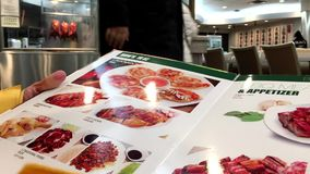 Motion of woman looking at menu turning pages stock video footage
