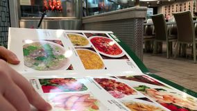 Motion of woman looking at menu turning pages. Inside Hon`s Chinese restaurant stock footage