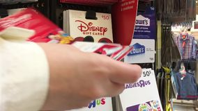 Motion of woman picking fifty dollars Disney gift card. Inside superstore stock video