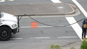 Motion of worker filling asphalt on road after big raining season stock footage