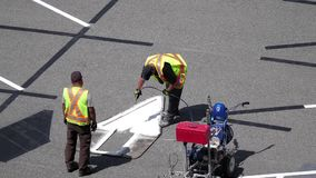 Motion of worker painting a new directional arrow. On a parking lot stock video footage