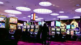 Motion of worker selling drink and people playing slot machine stock video footage
