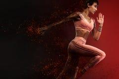 Motivação da aptidão e do esporte Velocista atlético, da mulher ou corredor forte e apto, correndo no fundo vermelho no fogo que  imagens de stock royalty free